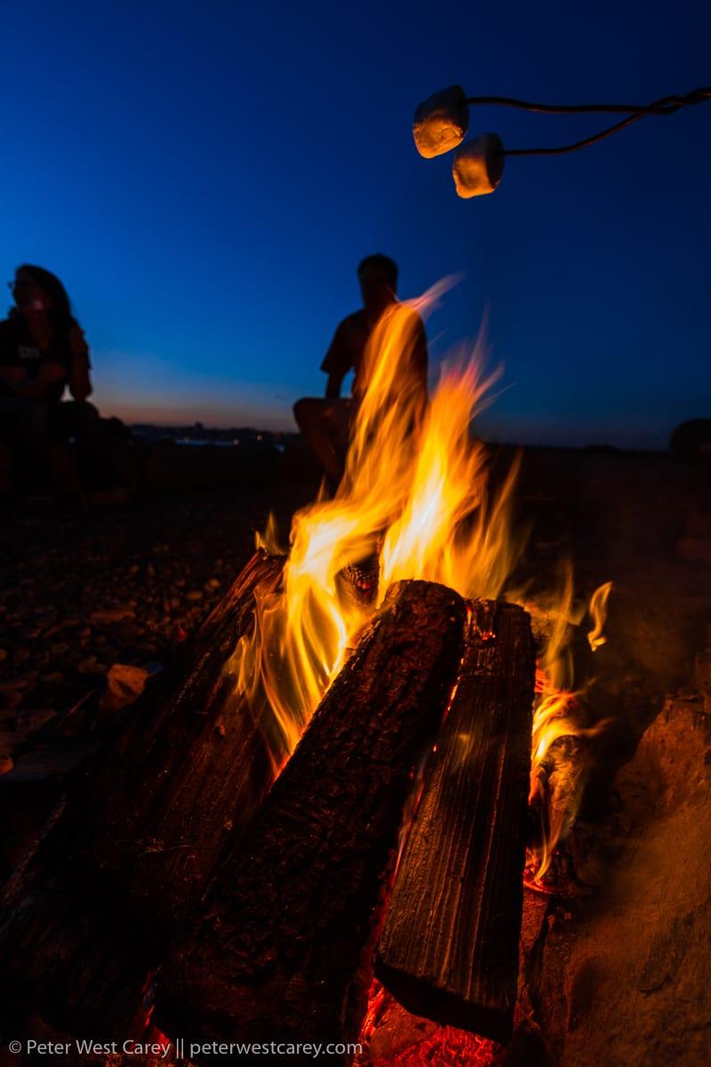 Couple sitting near campfire – USA – Washington – Bellingham