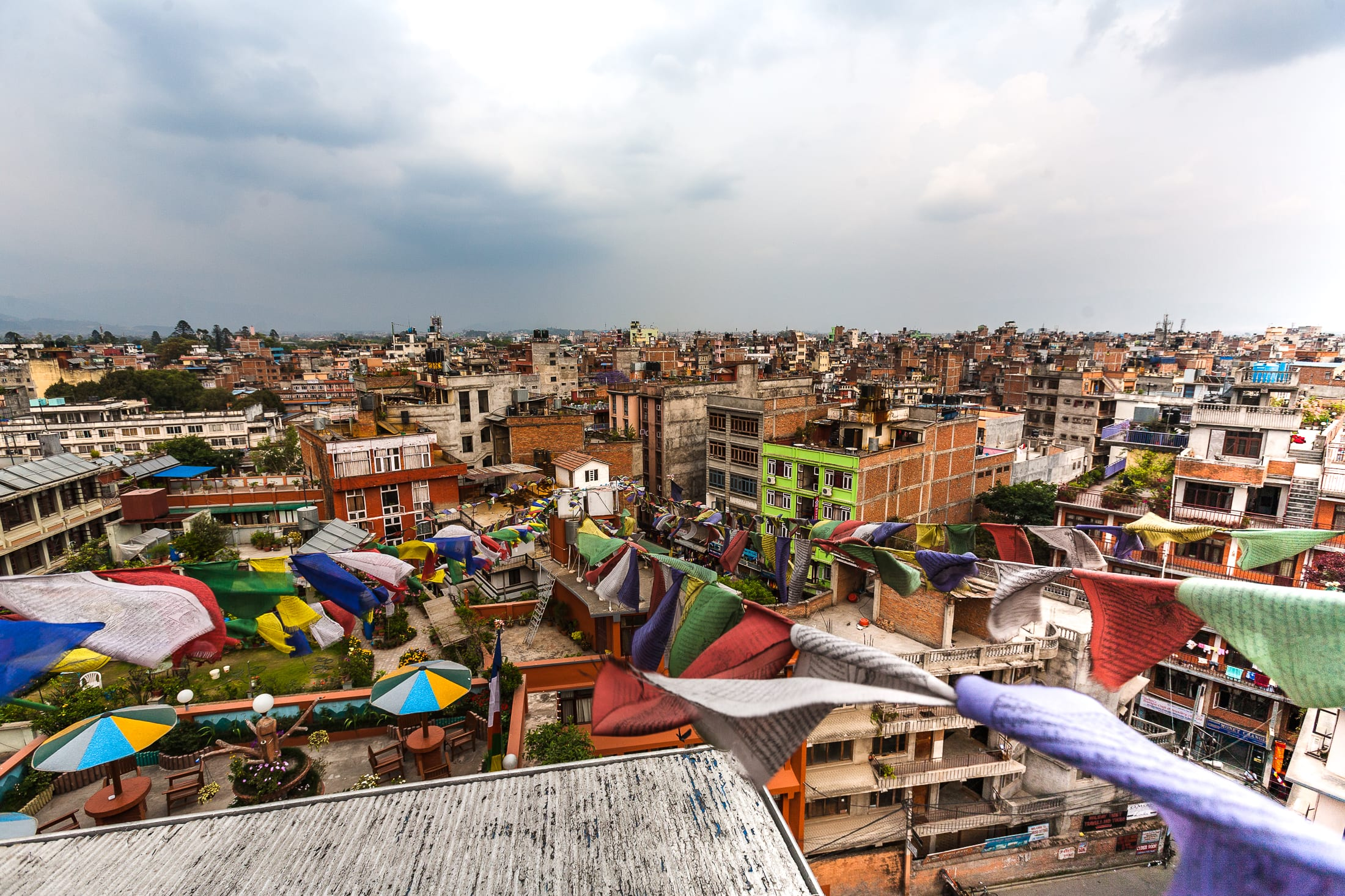 Multi-coloured prayer flags hanging over cityscape – Nepal